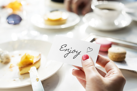 Woman holding a card with the word Enjoy