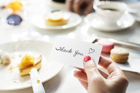 Woman holding a card with the word Thank You