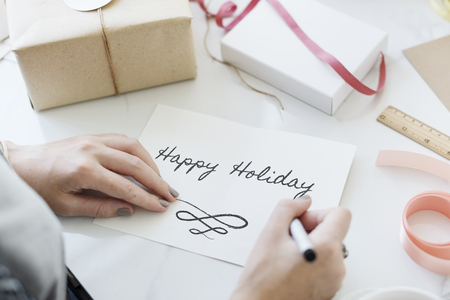 Woman writing Happy Holiday on a card