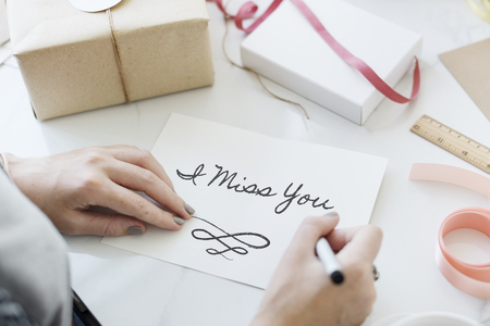 Woman writing I miss you on a card