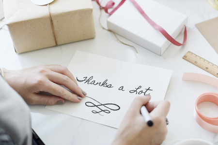 Woman writing thanks a lot on a card
