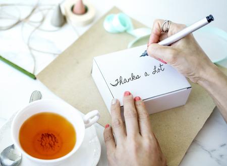 Woman writing Thanks a Lot on a box