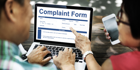 People using a laptop with complaint form