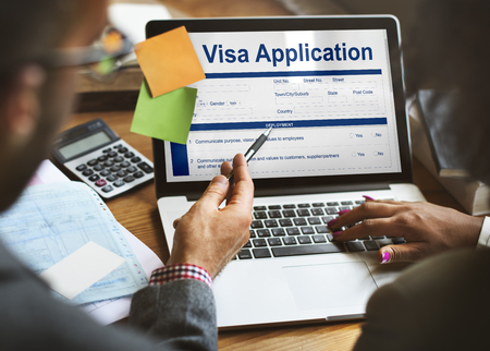 People using a laptop with visa application concept