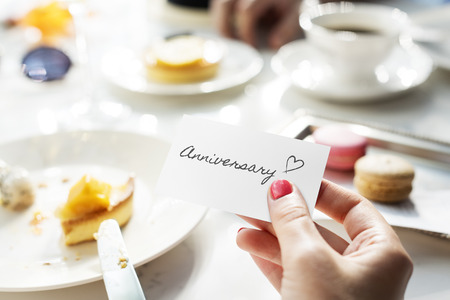 Woman holding a card with the word anniversary