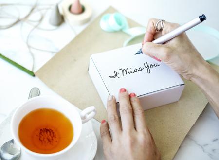 Woman writing I miss you on a box Reklamní fotografie - 111438556