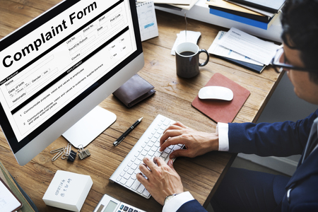Businessman at work with complaint form Stockfoto