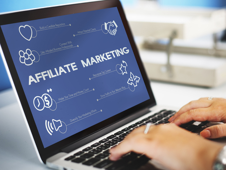 Person using a laptop with affiliate marketing concept Stock Photo