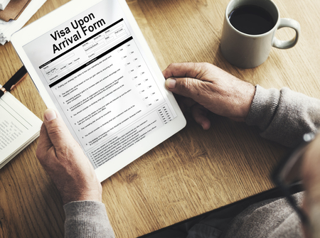 Man holding a digital tablet with visa upon arrival form Stock Photo
