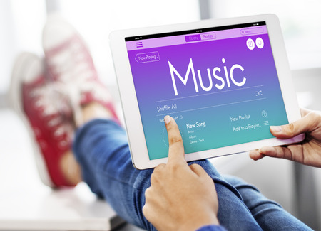 Woman using a digital tablet with music concept