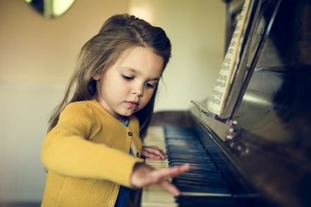 Adorable Cute Girl Playing Piano Concept Stockfoto