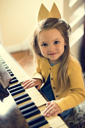 Adorable Cute Girl Playing Piano Concept Фото со стока