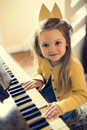 Entzückendes nettes Mädchen, das Klavier-Konzept spielt Standard-Bild - 65166470