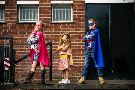 brother sister fight: Superheroes Kids Friends Brave Adorable Concept Stock Photo