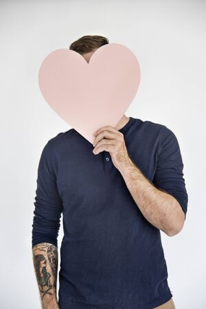 covering face: Man Holding Heart Sign Covering Face Concept