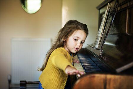 pianista: Adorable Cute Girl Playing Piano Concept Foto de archivo