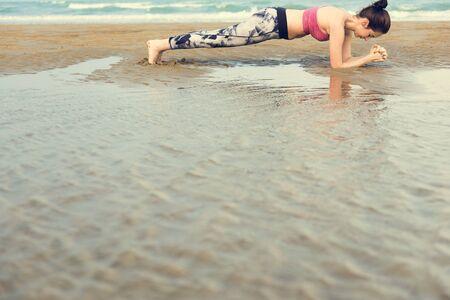 flex: Woman Planking Stretching Flex Training Healthy Lifestyle Beach Concept Stock Photo