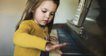 Adorable Cute Girl Playing Piano Concept Stock Photo