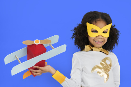Girl in superhero costume flying a plane