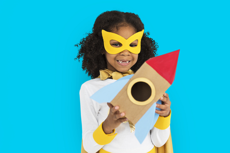 Girl with superhero costume holding a rocket