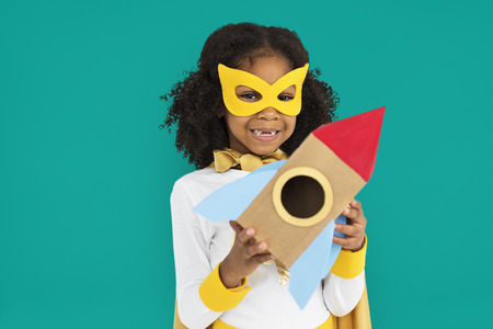 Girl with costume holding a toy rocket Imagens