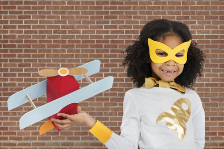 Girl with costume holding a toy plane