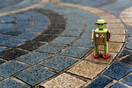 tin robot: Retro tin robot toy standing on ground with pattern