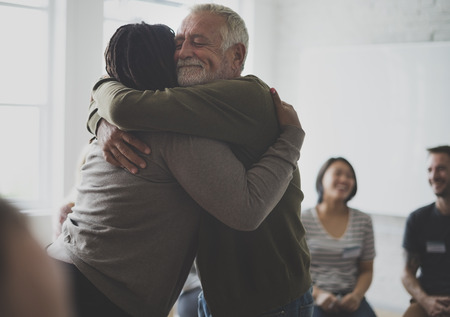community group: Old guy consoling a woman with a hug Stock Photo