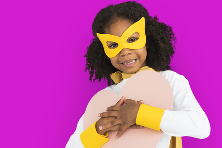 Girl in super hero costume hugging a heart