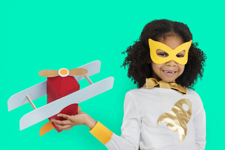 Girl in super hero costume holding a plane 스톡 콘텐츠