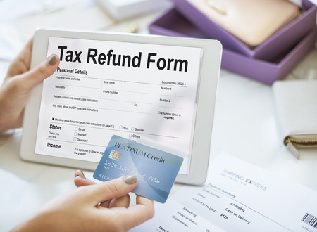 Credit card and tablet with tax refund form