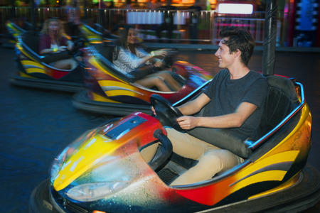 Young people playing bumper cars 写真素材
