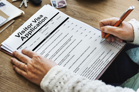 Person filling up a visitor visa application Stock Photo