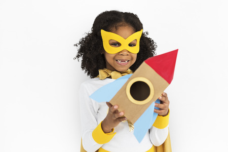 Girl in super hero costume holding a rocket Banco de Imagens