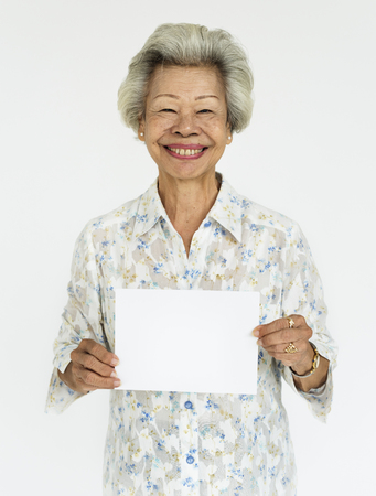 Elderly woman holding a blank placard Banque d'images - 111920667