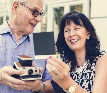 Senior couple checking instant film