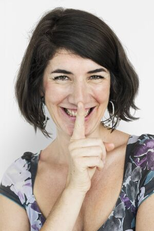 guardar silencio: Caucasian Lady Smiling Hand Gesture Keep Quiet Foto de archivo