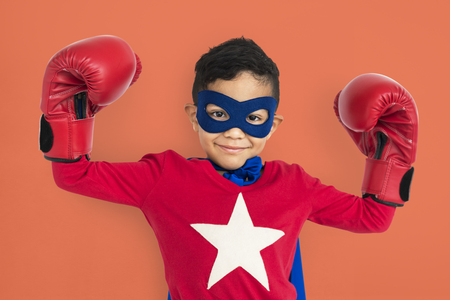 Boy in superhero costume with boxing gloves Stock Photo