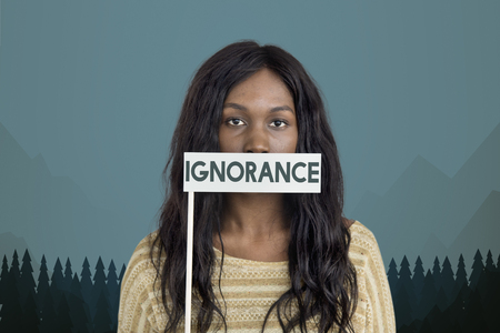 Woman with ignorance card covering her mouth