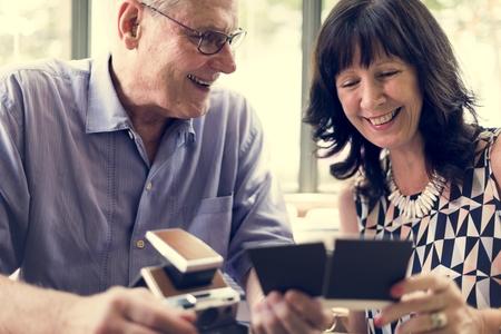 Senior couple checking instant film Imagens - 112584701