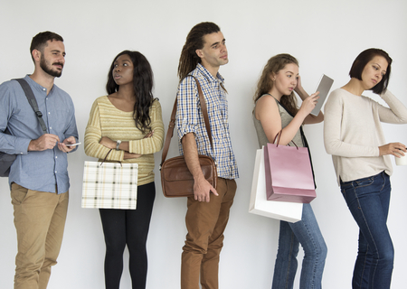 Diverse group of people standing in a queue Stock Photo