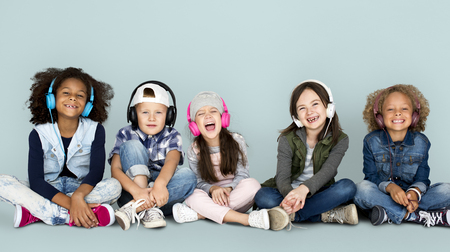 Group of Children Studio Smiling Wearing Headphones and Winter Clothes Stock Photo