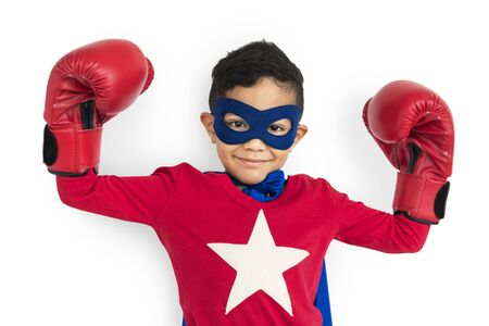 Cute young boy in a superhero costume and boxing gloves Stock Photo