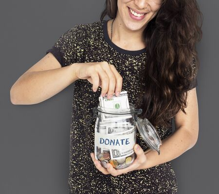 Young Woman Putting Money into a Donation Jar
