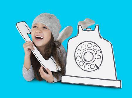 段ボールの電話の切り欠きに話している若い女の子
