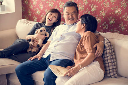 couple on couch: Asian family having fun in the living room together