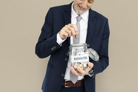 Businessman donating money in a jar 写真素材