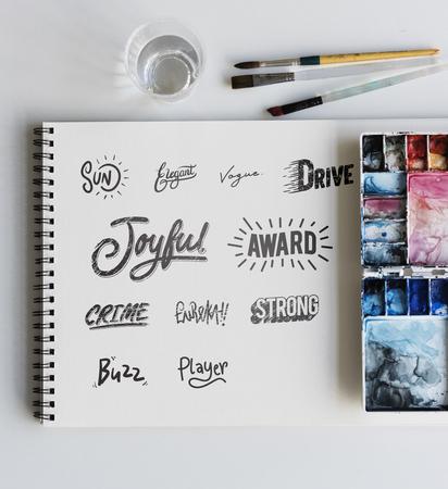 Palette Sketchbook Paper Brushes Words Design White Table Stock Photo - 75880136