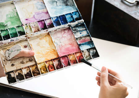 hand holding paper: Artist Painting Colors Illustration Stationery On Table
