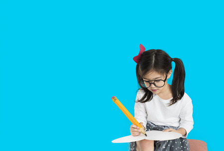 Little girl studio isolated writing on notebook